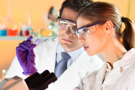 Foto de Attractive young scientist and her suprvisor looking at the microscope slide in the forensic laboratory. - Imagen libre de derechos