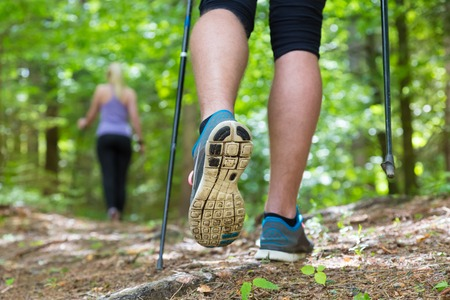 Foto de Young fit couple hiking in nature  Adventure, sport and exercise  Detail of male step, legs and nordic walking poles in green woods  - Imagen libre de derechos