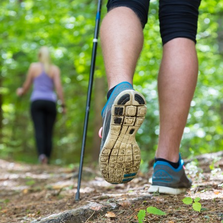 Photo for Young fit couple hiking in nature  Adventure, sport and exercise  Detail of male step, legs and nordic walking poles in green woods  - Royalty Free Image
