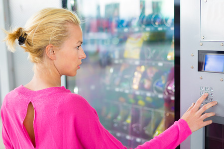 Photo pour Caucasian woman wearing pink top using a coin operated modern vending machine. Her hand is placed on the dial pad and she is looking on the small display screen. - image libre de droit