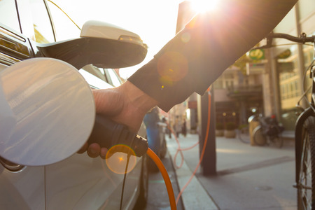 Photo pour Power supply for electric car charging.  Electric car charging station. Close up of the power supply plugged into an electric car being charged. - image libre de droit