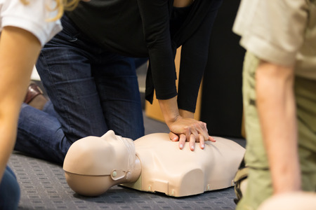 Photo pour A group of adult education students practitcing CPR chest compressioon on a dummy. - image libre de droit
