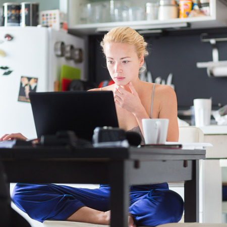 Photo for Female freelancer in her casual home clothing working remotly from her dining table in the morning. Home kitchen in the background. - Royalty Free Image