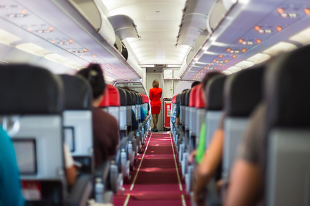 Photo for Interior of airplane with passengers on seats and stewardess in red uniform at the aisle. - Royalty Free Image