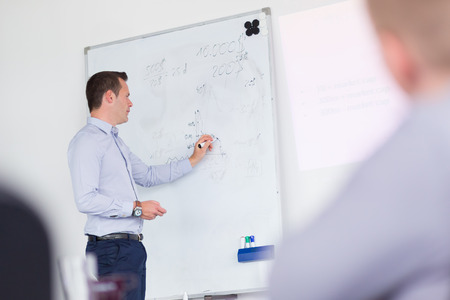 Foto de Businessman writing on whiteboard during his presentation on in-house business training, explaining business plans to his employees. - Imagen libre de derechos