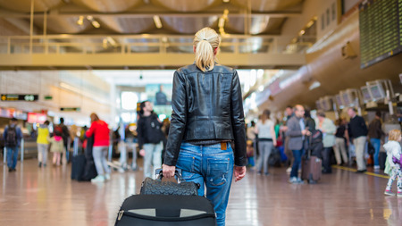 Photo for Casually dressed young stylish female traveller walking the airport terminal hall   draging suitcase and a handbag behind her. Blured background. Can also be used as railway, metro, bus station. - Royalty Free Image