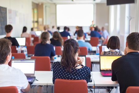Photo for Workshop at university. Rear view of students sitting and listening in lecture hall doing practical tasks on their laptops. - Royalty Free Image