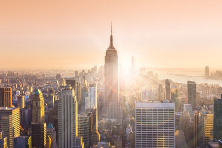 Photo pour New York City. Manhattan downtown skyline with illuminated Empire State Building and skyscrapers at sunset. Horizontal composition. Warm evening colors. Sunbeams and lens flare. - image libre de droit