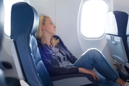 Foto de Tired blonde casual caucasian lady napping on uncomfortable seat while traveling by airplane. Commercial transportation by planes. - Imagen libre de derechos