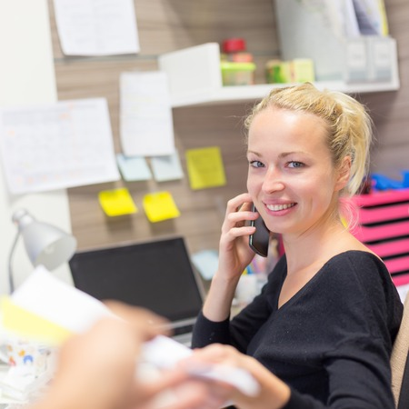Photo pour Business and entrepreneurship consept. Beautiful blonde business woman talking on mobile phone in colorful modern creative working environment accepting papers.  Female multi tasking. - image libre de droit