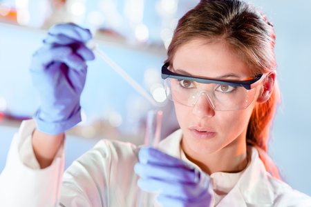 Foto de Life scientists researching in laboratory. Focused female life science professional pipetting solution into the glass cuvette. Lens focus on researcher's eyes. Healthcare and biotechnology concept. - Imagen libre de derechos