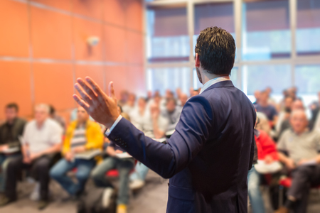 Photo for Speaker at Business Conference with Public Presentations. Audience at the conference hall. Entrepreneurship club. Rear view. Horisontal composition. Background blur. - Royalty Free Image