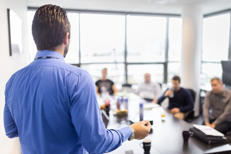 Foto de Business man making a presentation at office. Business executive delivering a presentation to his colleagues during meeting or in-house business training, explaining business plans to his employees. - Imagen libre de derechos