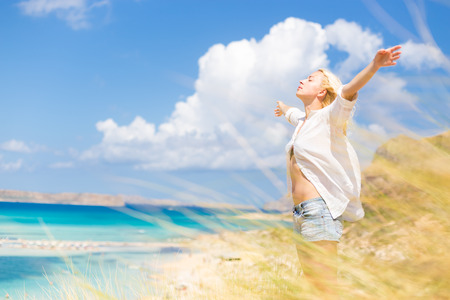 Photo pour Relaxed woman enjoying freedom and life an a beautiful sandy beach.  Young lady raising arms, feeling free, relaxed and happy. Concept of freedom, happiness, enjoyment and well being. - image libre de droit