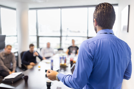Photo pour Business man making a presentation at office. Business executive delivering a presentation to his colleagues during meeting or in-house business training, explaining business plans to his employees. - image libre de droit