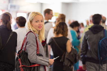 Photo pour Young blond caucsian woman waiting in line with plain ticket in her hands. Lady standing in a long queue to board a plane. - image libre de droit
