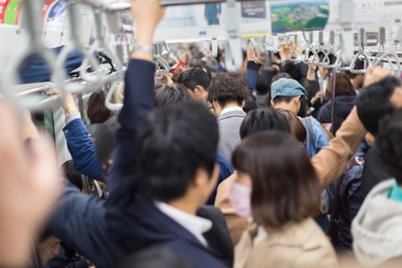 Photo pour Passengers traveling by Tokyo metro. Business people commuting to work by public transport in rush hour. Shallow depth of field photo. Horizontal composition. - image libre de droit