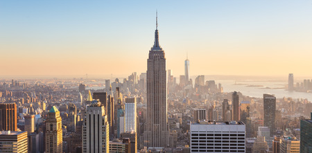 Foto de New York City. Manhattan downtown skyline with illuminated Empire State Building and skyscrapers at sunset seen from Top of the Rock observation deck. Vertical composition. - Imagen libre de derechos