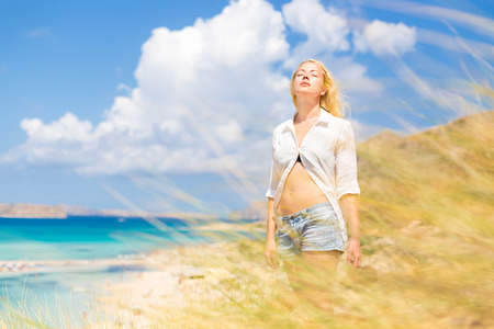 Photo pour Relaxed woman enjoying freedom and life an a beautiful sandy beach.  Young lady feeling free, relaxed and happy. Concept of freedom, happiness, enjoyment and well being.  Enjoying Sun on Vacations. - image libre de droit