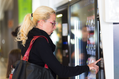 Foto de Casual caucasian woman using a modern beverage vending machine. Her hand is placed on the dial pad and she is looking on the small display screen. - Imagen libre de derechos
