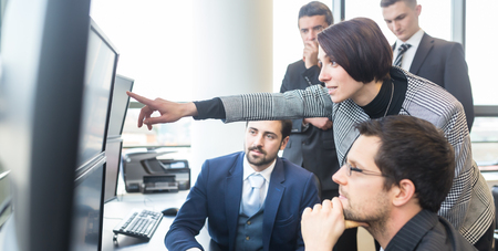 Foto de Business team looking at data on multiple computer screens in corporate office. Businesswoman pointing on screen. Business people trading online. Business, entrepreneurship and team work concept. - Imagen libre de derechos