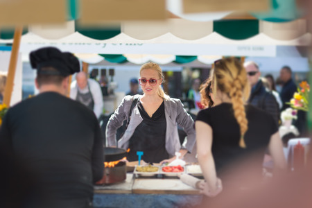 Foto de Beautiful blonde caucasian lady buying freshly prepared meal at a local street food festival. Urban international kitchen event in Ljubljana, Slovenia, in summertime. - Imagen libre de derechos