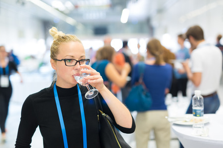 Photo pour Business woman, wearing name tag, drinking glass of water during coffee break at business meeting or conference. Abstract blurred people socializing n background. - image libre de droit
