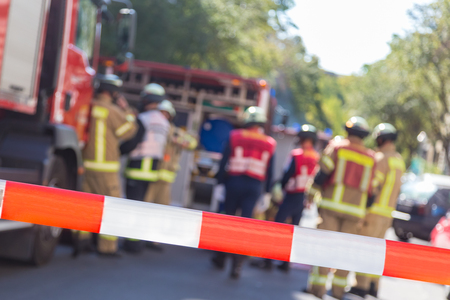 Photo pour Team of blured firefighters by firetruck on protected accident site. Focus on red and white security band. - image libre de droit