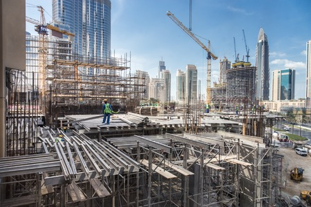 Photo for Laborers working on modern constraction site works in Dubai. Fast urban development consept. - Royalty Free Image