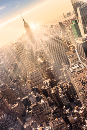 Photo pour New York City. Manhattan downtown skyline with illuminated Empire State Building and skyscrapers at sunset. Vertical composition. Warm evening colors. Sunbeams and lens flare. - image libre de droit