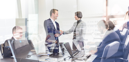 Photo for Sealing a deal. Business people shaking hands, finishing up meeting in corporate office. Businessmen working on laptop seen in glass reflection. Business and entrepreneurship concept. - Royalty Free Image