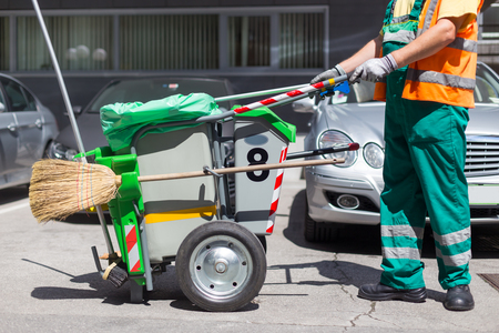 Photo pour Worker of cleaning company in green uniform with garbage bin and a broom. Utility service company men worker of municipality sweeping city streets. - image libre de droit