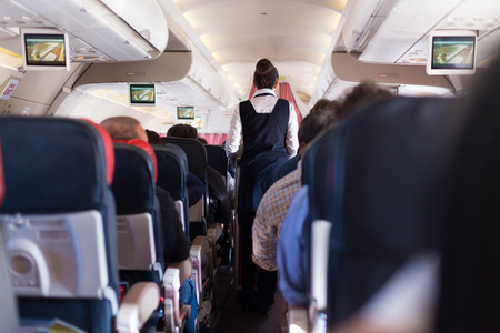 Foto de Interior of commercial airplane with passengers on seats during flight. Stewardess in dark blue uniform walking the aisle. Horizontal composition. - Imagen libre de derechos