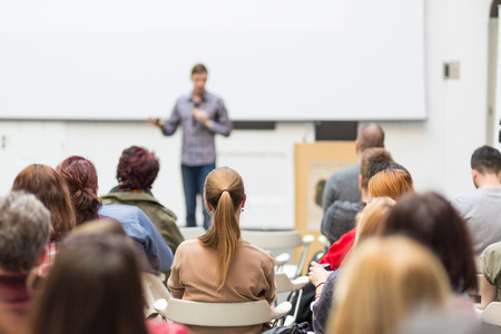 Foto de Male speaker giving presentation in lecture hall at university workshop. Audience in conference hall. Rear view of unrecognized participant in audience. Scientific conference event. - Imagen libre de derechos