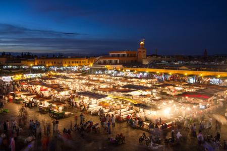 Foto per Jamaa el Fna market square at dusk, Marrakesh, Morocco, north Africa. Jemaa el-Fnaa, Djema el-Fna or Djemaa el-Fnaa is a famous square and market place in Marrakeshs medina quarter. - Immagine Royalty Free