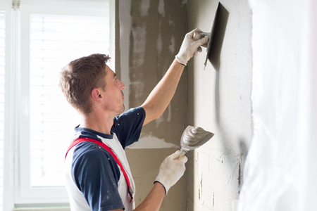 Photo pour Thirty years old manual worker with wall plastering tools renovating house. Plasterer renovating indoor walls and ceilings with float and plaster. - image libre de droit