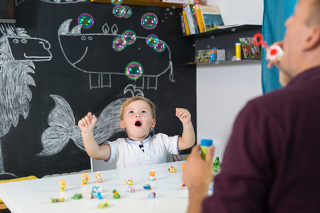 Foto de Cute little playfull toddler boy amazed by milky bubbles at child therapy session. Private one on one homeschooling with didactic aids. - Imagen libre de derechos