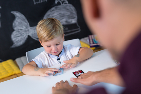 Foto de Cute little playfull toddler boy at child therapy session. Private one on one homeschooling with didactic aids. - Imagen libre de derechos