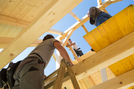 Foto de Roof builders mounting prefabricated wooden roof construction. Construction industry concept. - Imagen libre de derechos