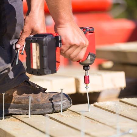 Foto de Laborer working with cordless battery electric screwdriver on construction site. - Imagen libre de derechos