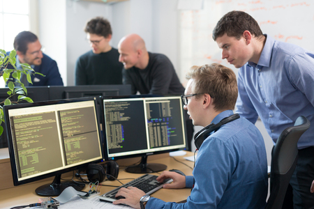 Photo for Startup business and entrepreneurship. Young software developers team brainstorming and programming on desktop computer in startup company share office space. - Royalty Free Image