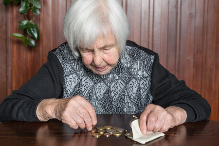Foto de Elderly 95 years old woman sitting miserably at the table at home and counting remaining coins from the pension in her wallet after paying the bills. - Imagen libre de derechos