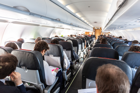 Foto de Interior of large commercial airplane with unrecognizable passengers on their seats during flight. - Imagen libre de derechos