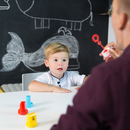 Foto de Cute little playfull toddler boy at speech therapy session. Private one on one homeschooling with didactic aids. - Imagen libre de derechos