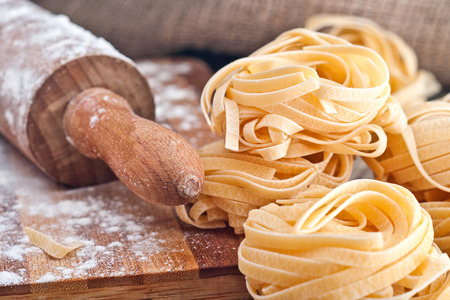 Foto de Homemade tagliatelle. Raw pasta on the wooden table. - Imagen libre de derechos