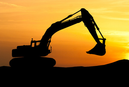 Photo for silhouette of Excavator loader at construction site with raised bucket over sunset - Royalty Free Image
