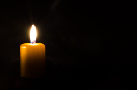 Photo for one burning candle decoration against black background - Royalty Free Image