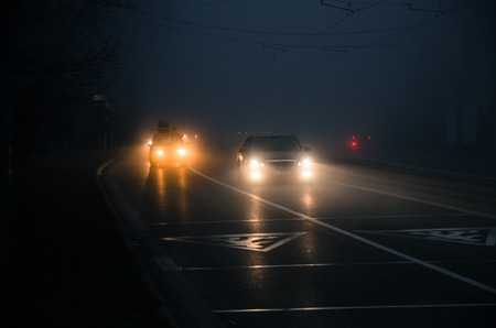 Photo for cars on road with lights on in foggy weather - Royalty Free Image