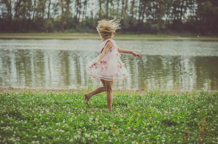 Foto de little girl with long blond hair in pink dress dancing at midnight in the green grass by the river - Imagen libre de derechos