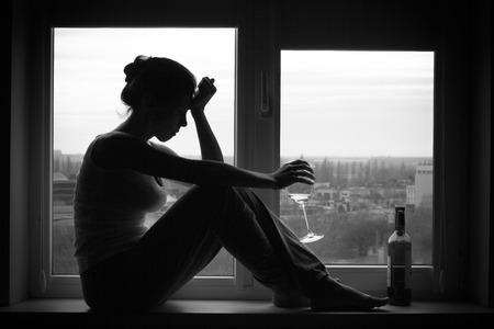 Foto de Sad young woman sitting on the window, drinks wine. Alcoholism problem. Black and white photography. - Imagen libre de derechos